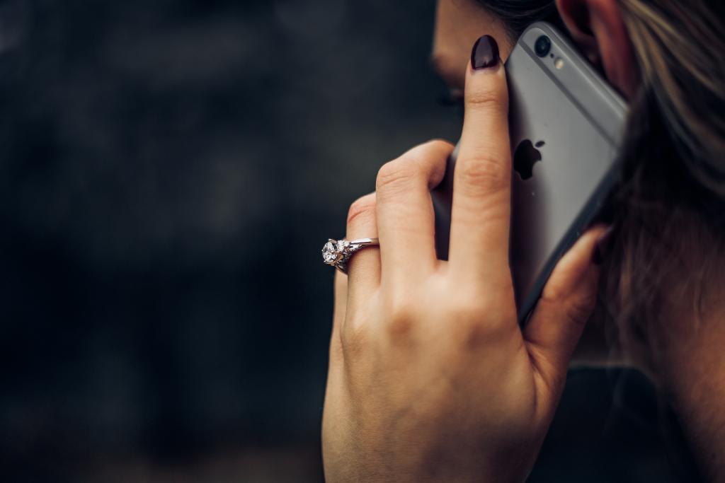 main avec bague en diamant et téléphone
